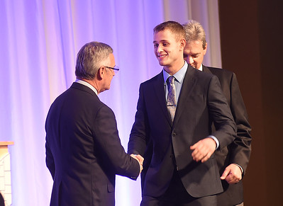 KRISTIN BAUER | CHRONICLE   Avon Lake High School wide receiver Carsen Toy shakes the hands of Jim Tressel and Larry Kehres on Tuesday night, March 7 during the Mike Cleary Northeastern Ohio Chapter of the National Football Foundation.