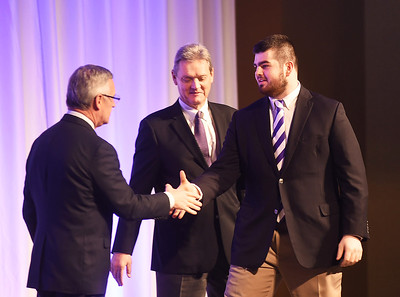 KRISTIN BAUER | CHRONICLE   Avon High School's center and defensive lineman Sam Gerak shakes the hands of Jim Tressel and Larry Kehres on Tuesday night, March 7 during the Mike Cleary Northeastern Ohio Chapter of the National Football Foundation.