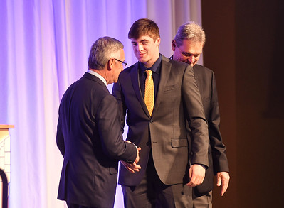 KRISTIN BAUER | CHRONICLE   Midview High School quarterback Dustin Crum shakes the hands of Jim Tressel and Larry Kehres on Tuesday night, March 7 during the Mike Cleary Northeastern Ohio Chapter of the National Football Foundation.