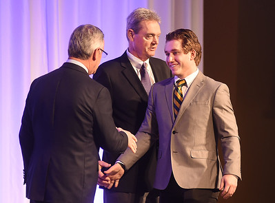 KRISTIN BAUER | CHRONICLE   St. Edward High School outside linebacker Mitchell O'Hara shakes the hands of Jim Tressel and Larry Kehres on Tuesday night, March 7 during the Mike Cleary Northeastern Ohio Chapter of the National Football Foundation.