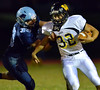 Archbishop Wood's Joe Dutkiewicz ,32, breaks the tackle of North Penn defender Michael Burns ,33, during first half action of their contest at North Penn High School.  Friday September 6,2013. Photo by Mark C Psoras/The Reporter
