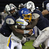 ANNA NORRIS/CHRONICLE<br /> Lorain's James Corbin (8) and Quentin Pardon (8) stop Olentangy's Jaden Konadu on the carry in the first half Friday night in the first round of playoffs in Division I at George Daniel Stadium in Lorain.