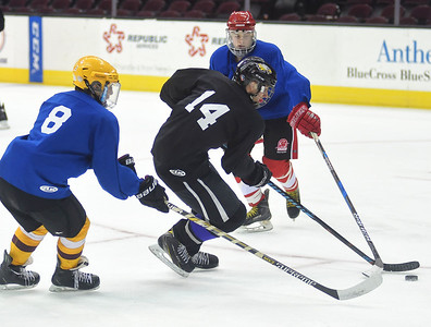 KRISTIN BAUER | CHRONICLE   Avon High School's Zach Zwierecki (14) goes to shoot the puck as he is guarded by Avon Lake High School's Trevor White (8) and Shaker Heights High School's Ryan Wheeler (3) guard him on Friday afternoon, March 17.