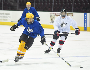 KRISTIN BAUER | CHRONICLE   Avon Lake High School's Alex Kelly takes the puck toward the goal as his teammate Trevor White (8) trails behind and Daniel Sternen (15) guards him on Friday afternoon, March 17.