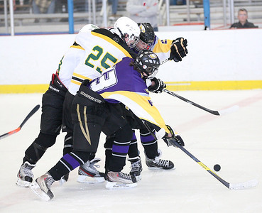 Avon's Neal Novot (13) and Christian Hierunymas (25) block Amherst's Paul Miller (25) from the puck. Another Amherst player is partially hidden behind Miller. photo by Ray Riedel