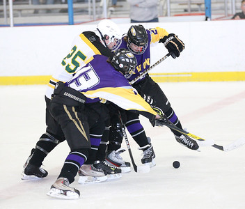 Avon's Neal Novot (13) and Christian Hierunymas (25) block Amherst's Paul Miller (25) from the puck. Another Amherst player is hidden behind Miller and Hierunymas. photo by Ray Riedel