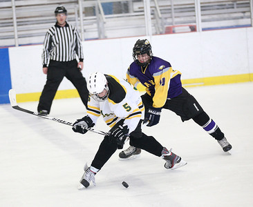 Amherst's Spencer Reavis (5) pursues the puck, followed by Avon's Braeden Friss (10). photo by Ray Riedel