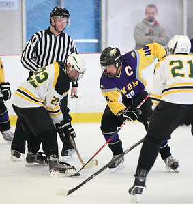 Face-off between Connor Morris (22) of Amherst and Hayden MacDoulald (48) of Avon. photo by Ray Riedel