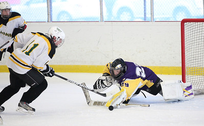 Amherst's Kevin Burgett knocks the puck past Avon goalie Joe Sefchick for a score. photo by Ray Riedel