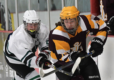Westlake's Austin Loosli crosses sticks with Avon Lake's defenseman Alex Kelly during hockey action Sunday at the Hamilton Ice Arena in Rocky River. BILL KEATON / CHRONICLE
