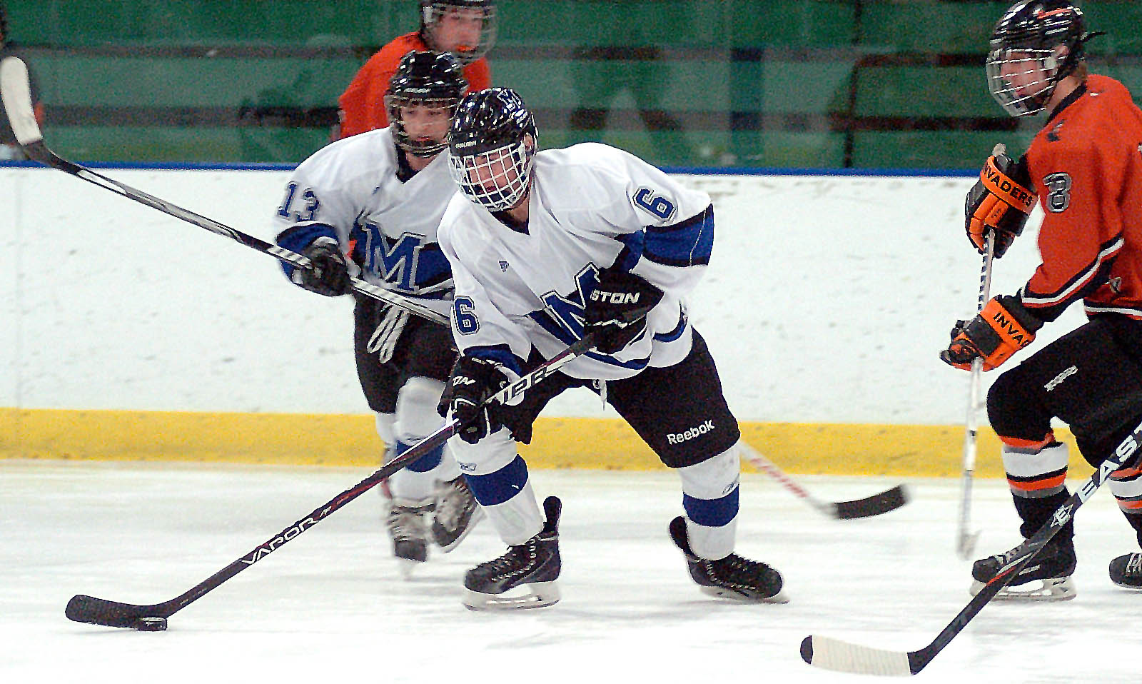 Midview's Jacob Scheetz, front, and Tommy Coon work the puck around Normandy's Jake Kerlin. LINDA MURPHY/CHRONICLE