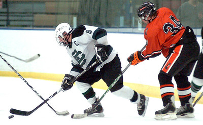 EC's #9 James Baker keeps the puck from Normandy's #34 Jack Pienta.