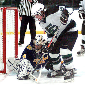 EC's #22 Stephen Donat tries to move his stick to knock the puck into the net but Olmsted Falls' goalie #4 Chris Polcar holds on to the stick with is glove while working with his stick to keep the puck out of the net.