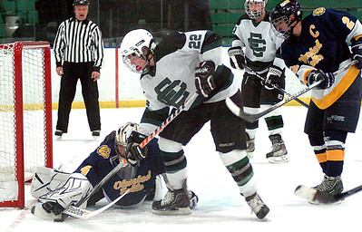 """EC's #22 Stephen Donat tries to move his stick to knock the puck into the net but Olmsted Falls' goalie #4 Chris Polcar holds on to the stick with his glove while working with his stick to keep the puck out of the net. Olmsted Fall""""s #2 is Tony Green."""