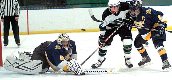 EC's #22 Stephen Donat tries to pop the puck over Olmsted Falls' goalie #4 Chris Polcar as he lunges to stop him. Olmsted Falls' #2 Tony Green keeps EC's #22 from advancing.