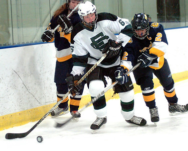 EC's #6 Nate Wilkie works the puck around the boards away from Olmsted Falls' #11 Ryan Norman and #2 Tony Green.