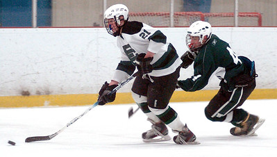 EC's #21 Ryan Saunders takes the puck down the ice with Westlake's #4 Ben Thurstons trying to trip him up.