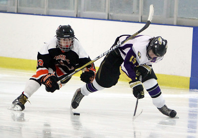 Avon's Neal Novotny brings the puck down the ice with pressure from Normandy's Mike Machalak in the second period Sunday afternoon at Serpentini Arena in Lakewood. ANNA NORRIS/CHRONICLE