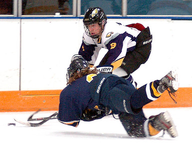 Avon's Nick Stevens fights for the puck as Olmsted Falls' Patrick Kerr leaps for the puck. LINDA MURPHY/CHRONICLE
