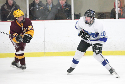 03Feb13___Midview's Brock Behler is about to launch the puck past Avon Lake defender Nate Nakels at North Park Ice Rink in Elyria. photo by Ray Riedel