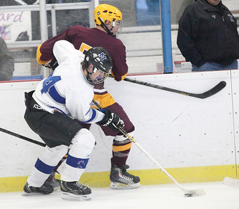 03Feb13___Midview's Bradley Urig takes the puck with Avon Lake's Jordan Herrera pressed against the boards. North Park Ice Rink in Elyria. photo by Ray Riedel