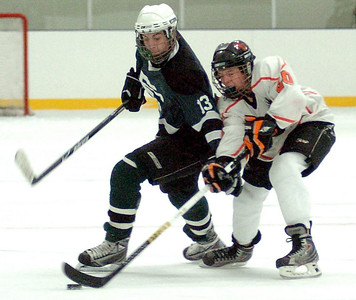 EC's #13 Bradley Oravets fights NO's #20 Brandon Schmitt for the puck.