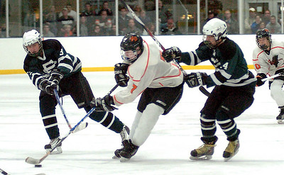 EC's #3 Brice Steindl fights NO's #7 Tim Musat for the puck as EC's #14 Zac Sommer joins the fight.