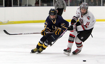 ANNA NORRIS/CHRONICLE Olmsted Falls' Zach Sadowski and Parma's Nick Ohmer chase down the loose puck in the first period Sunday afternoon in Parma.