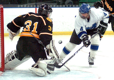 Midview's #4 Brad Urig takes a shot at goal and Cleveland heights goalie #31 Aidan Hall.