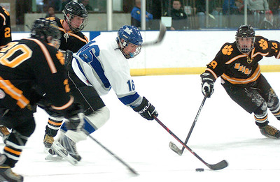 Midview's #16 KC Kudela takes the puck down the ice past Cleveland Heights' #19 Isac Brown.