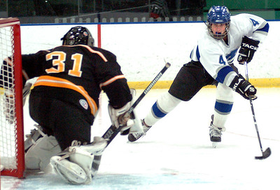 Midview's #4 Brad Urig takes the puck to Cleveland Hgts goalie #31 Aidan Hall.
