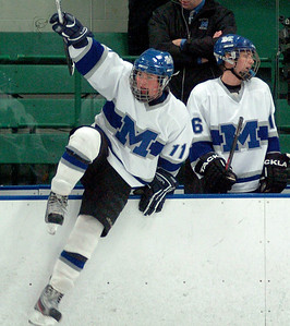 Midview's #11 Kyle Kudela leaps on to the ice to celebrate their win.