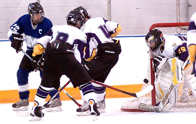 Midview's #22 Austin Steindl shoots the puck between Avon's #8 Nick Stevens and #4 Eric Novakovic towards the goal, but Avon goalie #29 Joe Sefchick keeps his eye on it and blocks it.