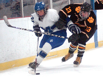 Midview's #13 Manny Ceja works the puck away from Cleveland Heights #13 Sam Brown.