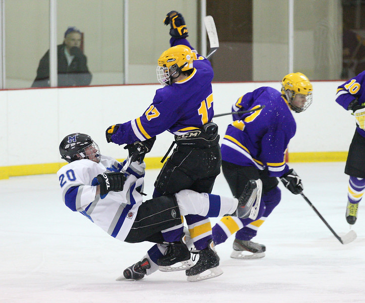 Midview's Brock Behler (20) takes a hard check by Lakewood's Victor Dobos and Lakewood's Matt Johnson takes the puck.  photo by Ray Riedel