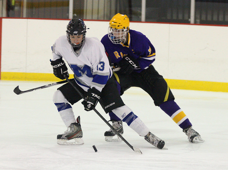 Manny Ceja (13) takes control of the puck in front of Lakewood captain Colin Scheel. photo by Ray Riedel