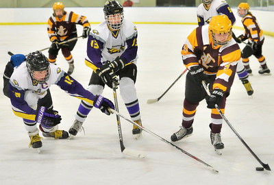 Corey McDevitt, right, of Avon Lake takes a shot against Avon's Jacob Folds, center, and Joe Goetz in the second period. DAVID RICHARD / CHRONICLE