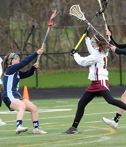 Avon Lake's Megan Twyman , right, takes a shot on goal over Kenston's Chloe Weber on April 27.  STEVE MANHEIM/CHRONICLE