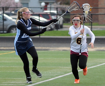 Avon Lake's Lauren Anthony (6) runs downfield past Kenston's Bridget Lucey on April 27.  STEVE MANHEIM/CHRONICLE