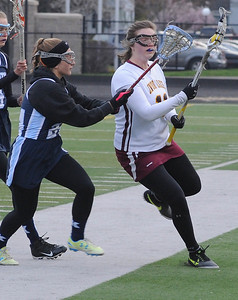 Avon Lake's Regan Rusher, right, and  Kenston's Erica Abbarno tangle during a lacrosse game Aprl 27.  STEVE MANHEIM/CHRONICLE