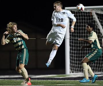 Highland's Joshua Woolard plays a ball between Firestone defenders Joey Aronhalt and Aaron Douglas during the first half. AARON JOSEFCZYK/GAZETTE