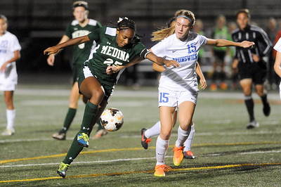 Medina's Janiece Joyner pushes the ball upfield while being defended by Brunswick's Maddy Grabowski in the first half. JUDD SMERGLIA / GAZETTE