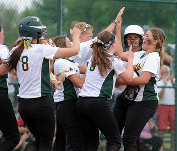 Amherst players meet Madison Spataro, right, after she hit the game-winning single in the seventh inning of a regional  semifinal in Clyde on May 25.  STEVE MANHEIM/CHRONICLE