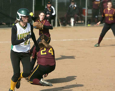 Avon Lake pitcher #16 Annie Wennerberg fires a throw to first; ducking is teammate #24 Emily Young, who came in for the short hit; Amherst's #26 Madison Heffley was out.   photo by Chuck Humel