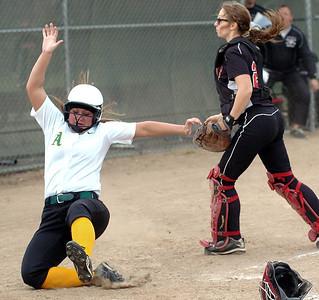 Amherst's runner #11 Katelyn Pittman slides safely home as Perkins' catcher #21 Shannon Matso goes for the ball.