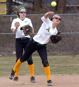 After catching a pop fly, Amherst's #2 Ashley Cogdell throws to first base. Amherst's #1 Lauren Farley backs her up.