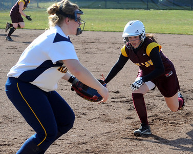 Avon Lake Lauren Kuzniar slides back safely to first base in front of North Ridgeville Brittany Helmink Mar. 31.   Steve Manheim