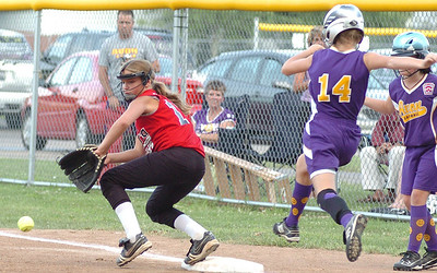 Top of 1st - Elyria's #12 Aubrey Frazier tries to stop the ball as Avon's #14 Maddy Cromling crosses 1st base safely
