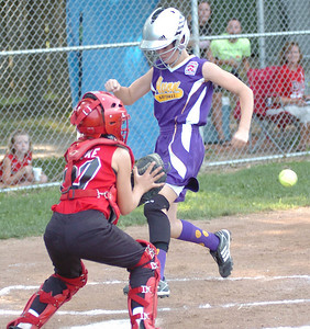 Top of 3rd - Avon's #14 Maddy Cromling crosses home plate safely as Elyria's #00 Emmalee Cooke waits for the ball.