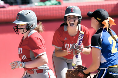 Elyria's Dierra Hammons, center, cheers as teammate Riley Zana scores on a passed ball in the first inning. DAVID RICHARD / CHRONICLE